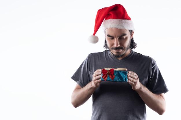 Porträt des latino-mannes mit weihnachtsmütze, die geschenke betrachtet. weißer hintergrund