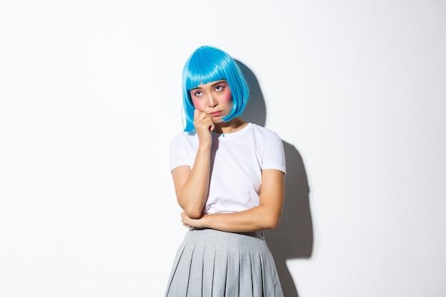Porträt des launischen niedlichen asiatischen mädchens in der blauen parteiperücke, die traurig oder gelangweilt fühlt, ungerührt in der oberen linken ecke schaut, stehend.