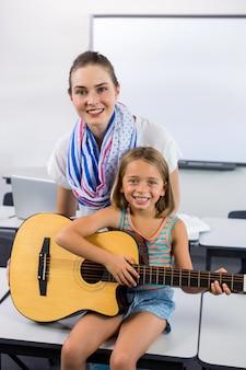 Porträt des lehrers, der mädchen hilft, gitarre im klassenzimmer zu spielen