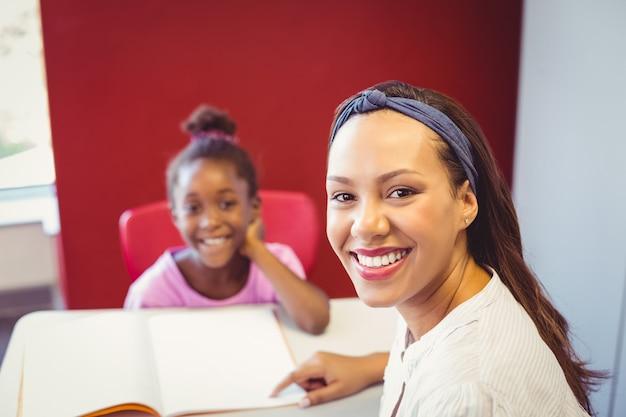Porträt des lehrers einem mädchen bei ihren hausaufgaben im klassenzimmer helfend
