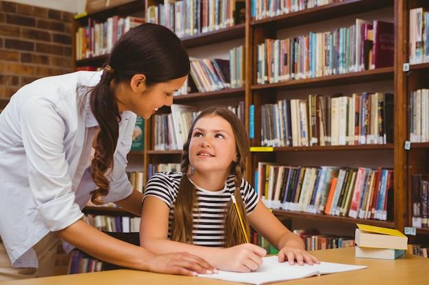 Porträt des lehrers kleines mädchen mit hausarbeit in der bibliothek unterstützend
