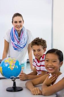 Porträt des lehrers mit jungen und mädchen im klassenzimmer