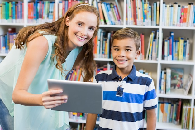 Porträt des lehrers und des schuljungen, der digitale tablette in der bibliothek verwendet