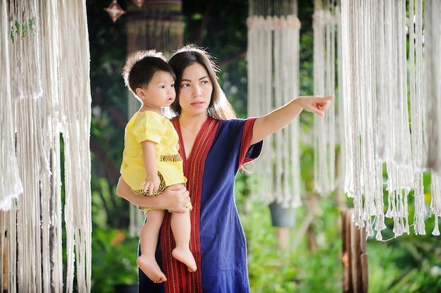 Porträt des lernens der jungen mutter und des babys im freien, fällend, entspannen sie sich in der landschaft.