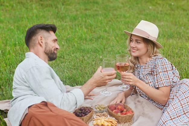 Porträt des liebenden erwachsenen paares, das picknick auf grünem gras genießt und weingläser während des romantischen dates im freien klirrt