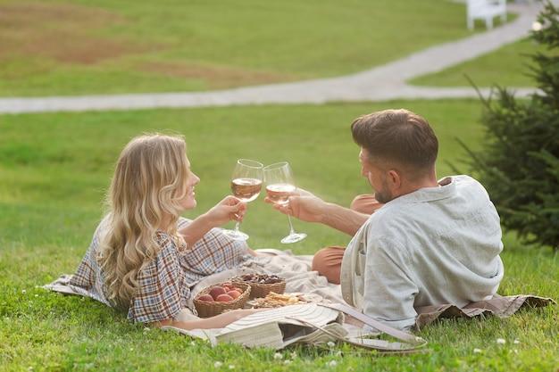 Porträt des liebenden erwachsenen paares, das picknick im sonnenlicht genießt und weingläser während des romantischen dates im freien klirrt