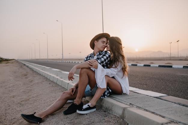 Porträt des liebenden paares, das küsst, während es neben der autobahn sitzt, nachdem es im sommerwochenende durch die stadt gereist ist. freudige langhaarige frau, die ihren freund sanft umarmt und sich bei sonnenuntergang in der nähe der straße ausruht
