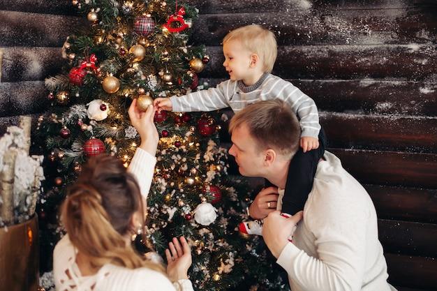 Porträt des liebenden vaters mit tochter auf seinen schultern, die schönen weihnachtsbaum mit spielzeug und dekoration zu hause verzieren