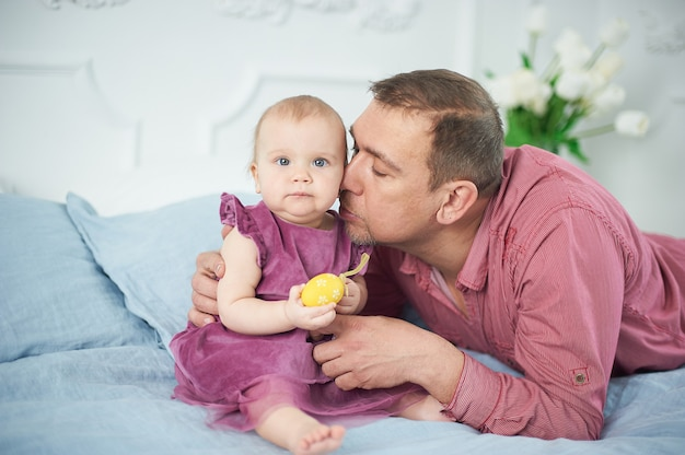 Porträt des liebevollen vaters spielend mit ihren 10 monaten alten baby im schlafzimmer.
