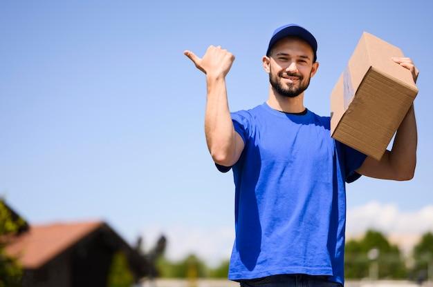Porträt des lieferboten, der pappkarton trägt
