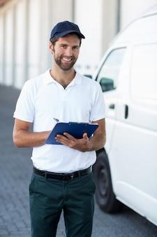 Porträt des lieferers, der ein klemmbrett neben seinem van hält