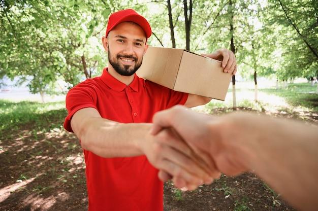 Porträt des liefermanns, der dem kunden die hand schüttelt