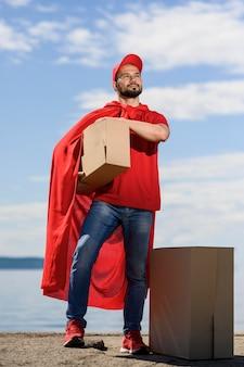 Porträt des liefermanns, der superheldenumhang trägt