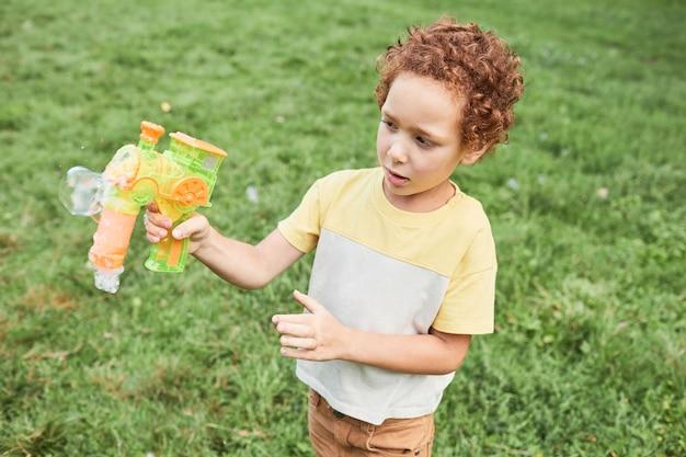 Porträt des lockigen jungen, der draußen im parkkopierraum mit blasenspielzeug spielt