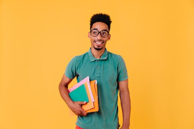 Porträt des lustigen afrikanischen studenten im grünen t-shirt. foto des glückseligen schwarzen jungen in den gläsern, die bücher und lehrbücher nach prüfungen halten.