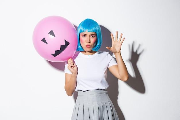 Porträt des lustigen asiatischen mädchens, das versucht, jemanden an halloween zu erschrecken, blaue perücke tragend und rosa ballon mit gruseligem gesicht haltend.