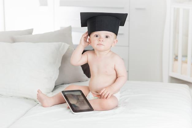 Porträt des lustigen babys in der abschlusskappe mit digitaler tablette. konzept des babygenies