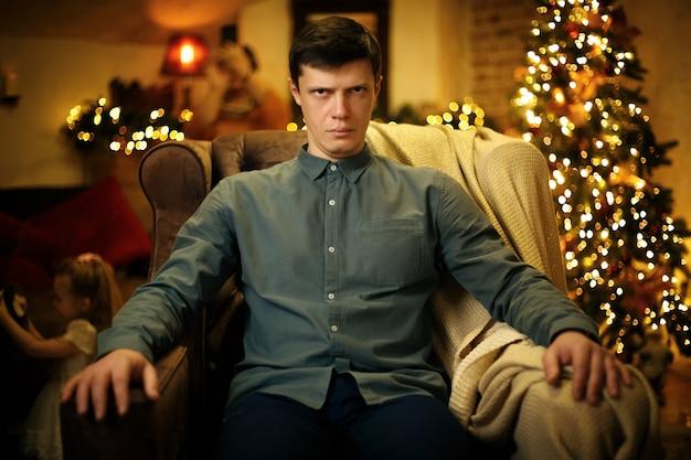 Porträt des lustigen ernsten müden jungen vaters im sessel vor dem hintergrund eines weihnachtsbaums
