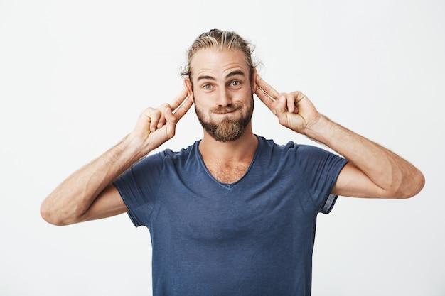 Porträt des lustigen gutaussehenden mannes mit bart, der dumme gesichter macht und mit händen gestikuliert