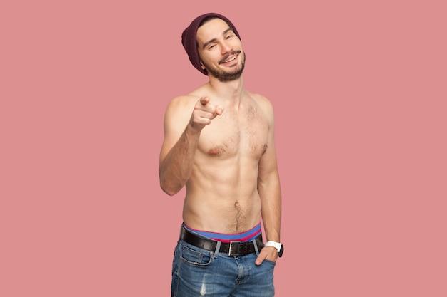 Porträt des lustigen hübschen nackten hemdlosen jungen bärtigen mannes, der mit zahnigem lächeln und verführergesicht steht, schaut und auf die kamera zeigt. indoor-studioaufnahme, isoliert auf rosa hintergrund.