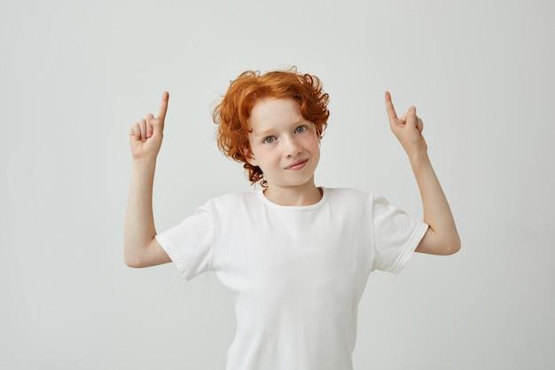 Porträt des lustigen ingwerkindes mit den sommersprossen, die oben auf weiße wand mit entspanntem ausdruck zeigen