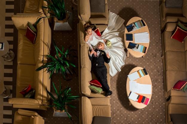 Porträt des lustigen jungen gerade verheirateten paares, das auf einem sofa liegt