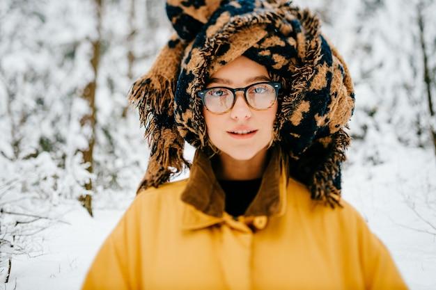 Porträt des lustigen jungen hipster-mädchens in den gläsern mit dem turban des schals, der im wald aufwirft