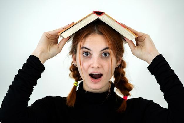 Porträt des lustigen jungen lächelnden studentenmädchens mit einem offenen buch auf ihrem kopf. lese- und bildungskonzept.