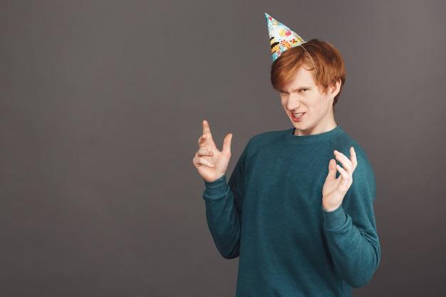 Porträt des lustigen jungen rothaarigen kerls im grünen pullover und im partyhut, die hände mit ekelausdruck ausbreiten