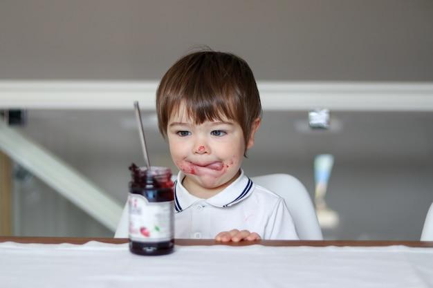 Porträt des lustigen kleinen jungen, der glasgefäß mit kirschmarmelade mit seiner zunge heraus und schmutzigem gesicht betrachtet