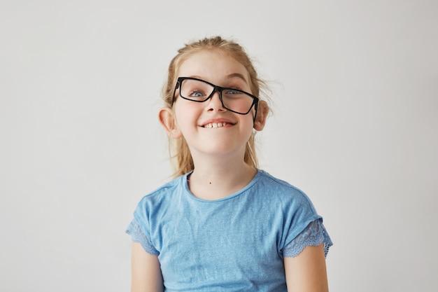 Porträt des lustigen kleinen mädchens mit blauen augen und hellem haar im blauen hemd, das spaß mit der brille des vaters hat. glückliches kindheitskonzept.