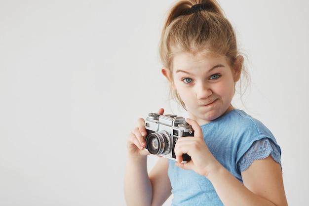 Porträt des lustigen kleinen mädchens mit blonden haaren in der schwanzfrisur, mit albernem ausdruck, kamera in händen haltend, um ein bild zu machen.