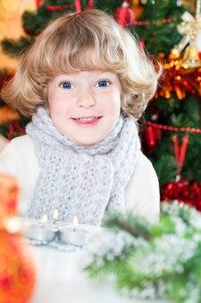 Porträt des lustigen lächelnden kindes gegen verzierten weihnachtshintergrund