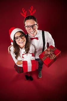 Porträt des lustigen paares mit weihnachtsgeschenk