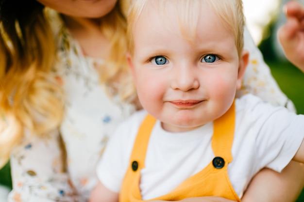 Porträt des lustigen reizenden kleinen jungen in mamas armen