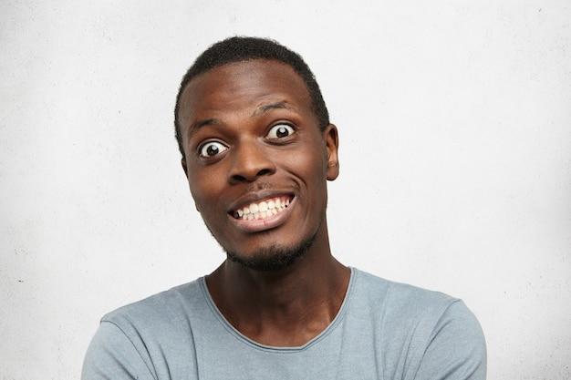 Porträt des lustigen verängstigten jungen afrikanischen mannes, der augen herauswacht und zähne zeigt