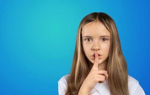 Porträt des mädchenkindes finger auf ihren lippen halten und bitten, ruhig zu bleiben