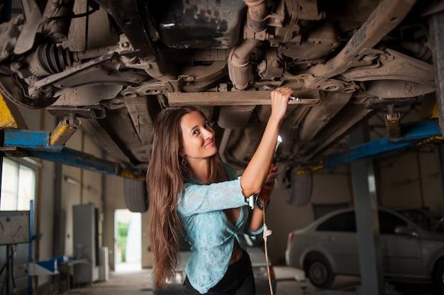 Porträt des mädchens angehobenes auto an der autowerkstatt überprüfend