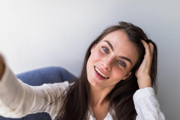Porträt des mädchens, das ein selbstporträt mit ihrem smartphone zu hause nimmt.