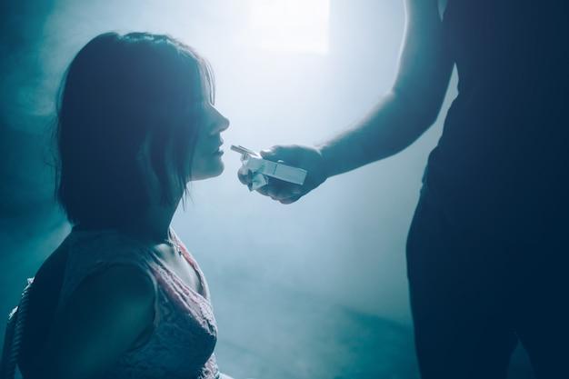 Porträt des mädchens, das gefesselt sitzt und kleine schachtel zigaretten betrachtet, die der kerl im schwarzen hemd vor ihr hält