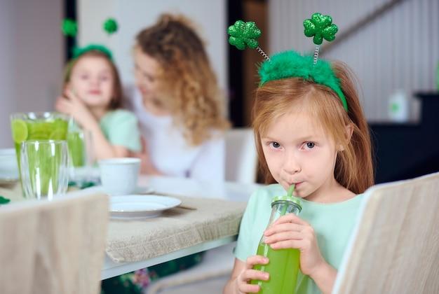 Porträt des mädchens, das grünen cocktail trinkt