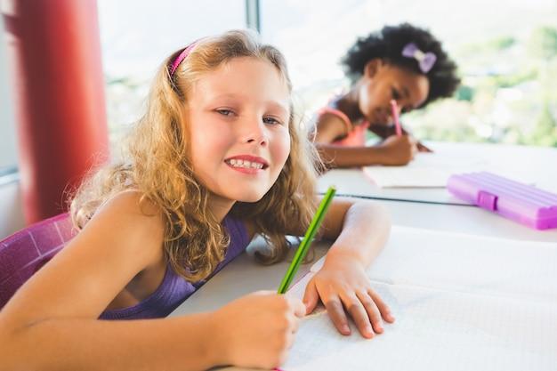 Porträt des mädchens, das hausaufgaben im klassenzimmer macht