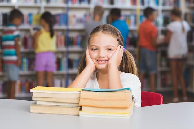Porträt des mädchens, das mit stapel bücher in der bibliothek sitzt