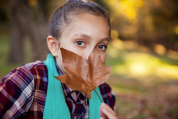 Porträt des mädchens, das mund mit herbstblatt versteckt