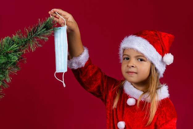 Porträt des mädchens, das santa kleidung und roten hut trägt, der den weihnachtsbaum mit einer medizinischen schutzmaske, isolierte rote wand verziert. neue normale konzeptferien.