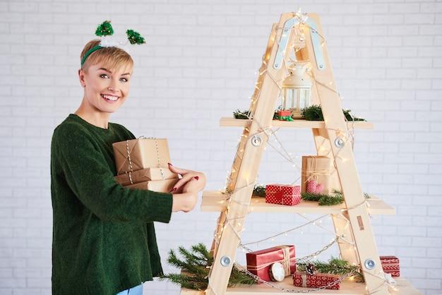 Porträt des mädchens, das stapel von weihnachtsgeschenken hält
