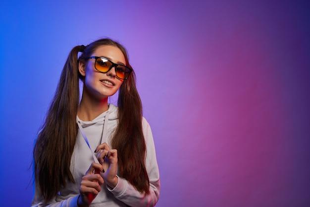 Porträt des mädchens, das trendige getönte gelbe linsensonnenbrille im neonlicht trägt. hipster teenager in gläsern.