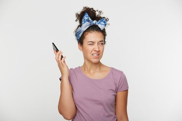 Porträt des mädchens hält das telefon auf abstand vom kopf in der hand
