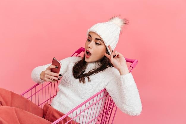 Porträt des mädchens im leichten strickoutfit im rosa wagen auf isolierter wand. frau schaut überrascht in smartphone und zeigt friedenszeichen.