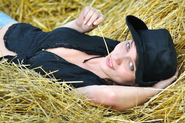 Porträt des mädchens im schwarzen cowboyhut und im hemd liegt auf dem rücken auf dem heuhaufen, hält stroh in den zähnen